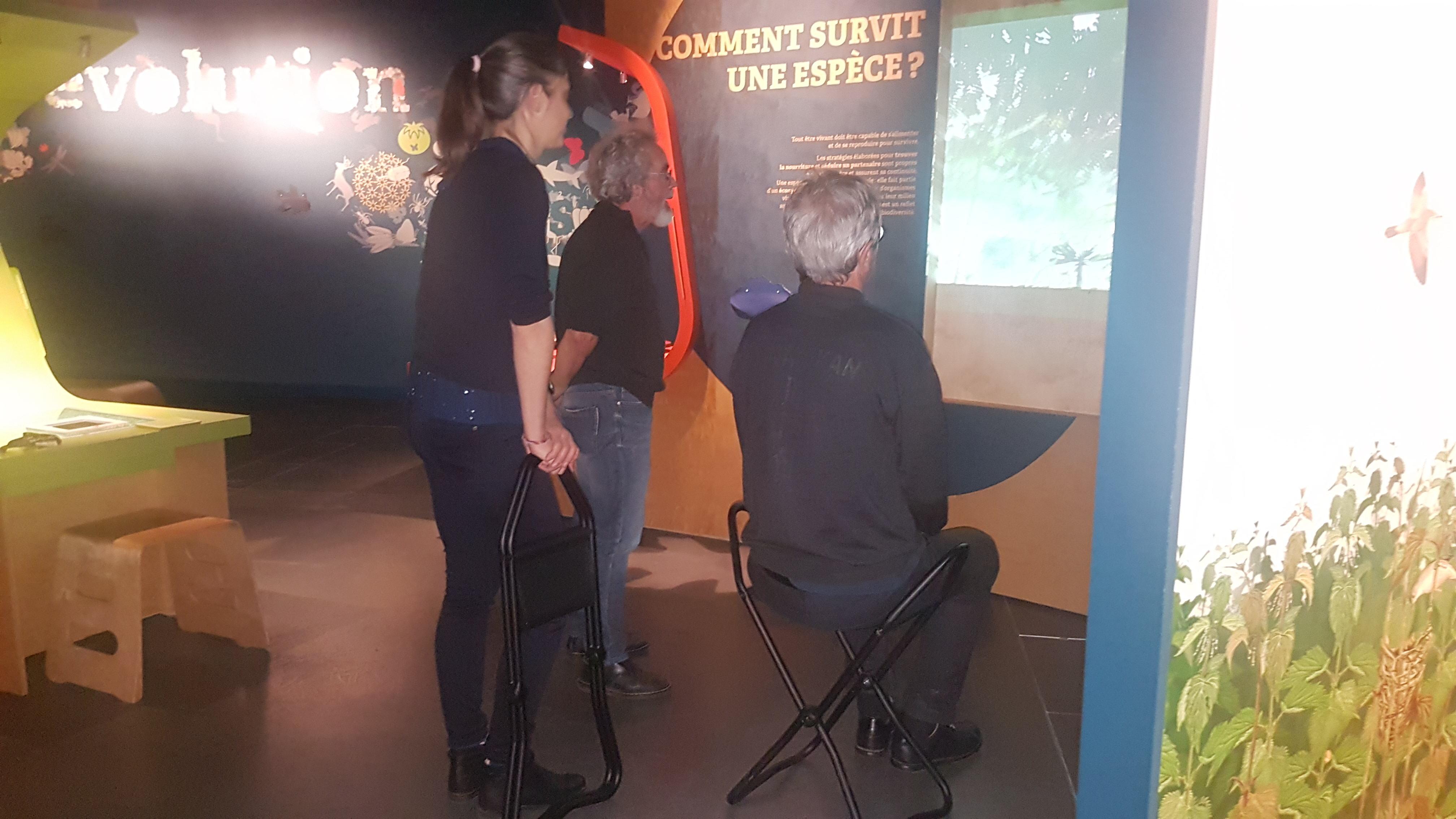 légende photo : dans l'Espace des sciences, 3 personnes regardent une vidéo, l'une âgée est assise sur une canne-siège, une autre est en appui sur une canne-siège repliée.